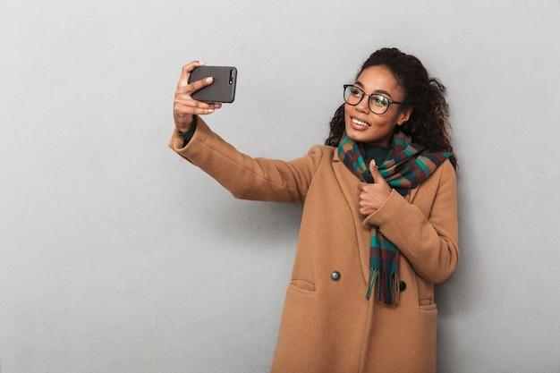 Uśmiechnięta afrykańska kobieta ubrana w stojący płaszcz, biorąc selfie z telefonem komórkowym