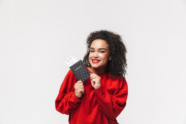 Uśmiechnięta afrykańska kobieta w czerwonym swetrze trzymająca paszport z biletami i patrząca bezpośrednio na szarym tle