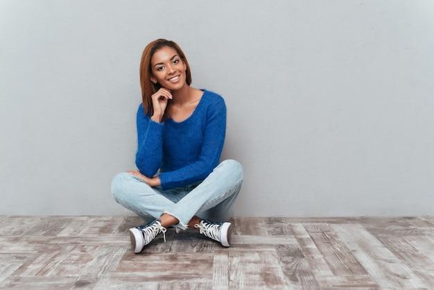 Uśmiechnięta afrykańska kobieta w swetrze i dżinsach siedzi na drewnianej podłodze i trzyma jedną rękę blisko twarzy