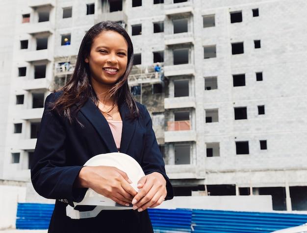 Uśmiechnięta amerykanin afrykańskiego pochodzenia dama trzyma zbawczego hełm blisko budynku w budowie