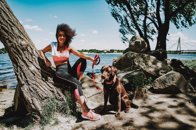 Uśmiechnięta amerykanin afrykańskiego pochodzenia dziewczyna z psem outdoors.