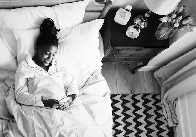 Uśmiechnięta amerykanin afrykańskiego pochodzenia kobieta na łóżku używać telefon komórkowego