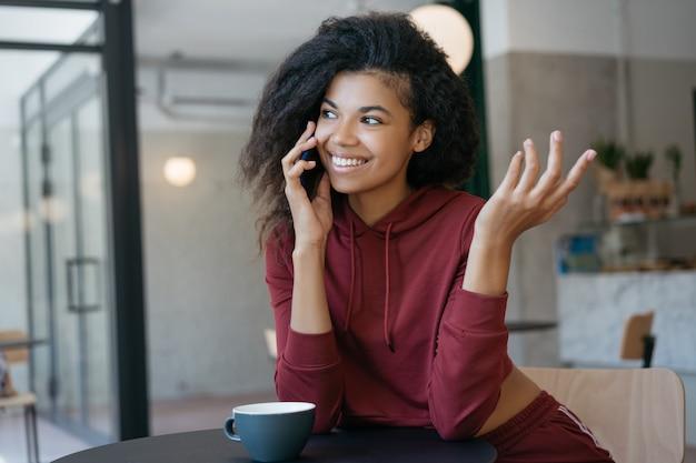 Uśmiechnięta amerykanin afrykańskiego pochodzenia kobieta opowiada na telefonie komórkowym, komunikacja, siedzi w nowożytnej kawiarni