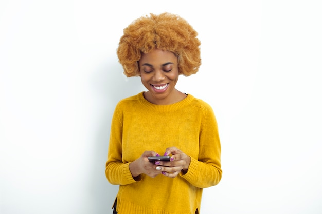 Uśmiechnięta amerykanin afrykańskiego pochodzenia kobieta trzyma telefon komórkowego. piękna czarna dziewczyna używa smartfona