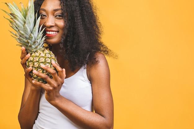 Uśmiechnięta amerykańska afrykańska kobieta trzyma ananasa