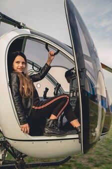 Uśmiechnięta animowana dziewczyna siedzi na siedzeniu drugiego pilota w helikopterze
