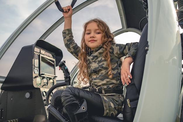 Uśmiechnięta animowana dziewczyna w kamuflażowej sukience siedząca w kokpicie helikoptera