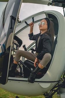 Uśmiechnięta animowana dziewczyna w lustrzanych okularach, patrząca w niebo z kokpitu helikoptera