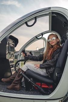 Uśmiechnięta animowana dziewczyna w lustrzanych okularach siedząca w otwartym helikopterze