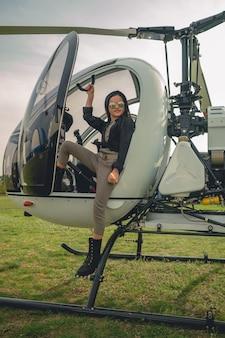 Uśmiechnięta animowana dziewczyna w lustrzanych okularach stojąca na podnóżku helikoptera