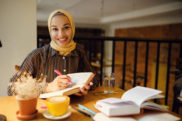 Uśmiechnięta arabska dziewczyna w hidżabie trzyma notatnik, wnętrze kawiarni uniwersyteckiej na tle. muzułmanka z książkami siedzi w bibliotece.