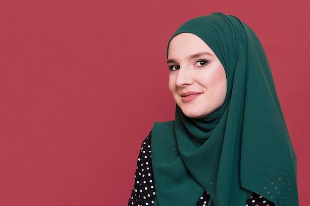Uśmiechnięta arabska kobieta patrzeje kamerę