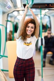 Uśmiechnięta arabska kobieta wśrodku metra pociągu