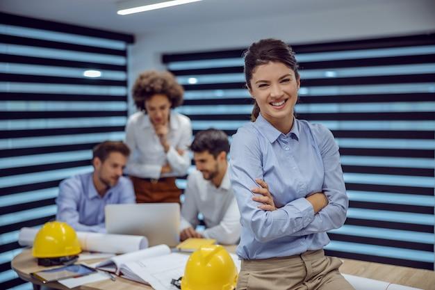 Uśmiechnięta architekt kobieta siedzi na stole w sali konferencyjnej z rękami skrzyżowanymi. koledzy pracujący nad projektem i patrząc na laptopa.