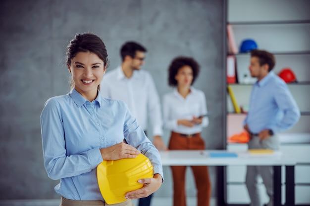 Uśmiechnięta architekt kobieta stojąc w biurze i trzymając kask, patrząc na przód