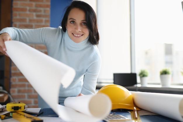 Uśmiechnięta architekt żeński trzymając biały papier whatman. koncepcja rozwiązań architektonicznych elewacji