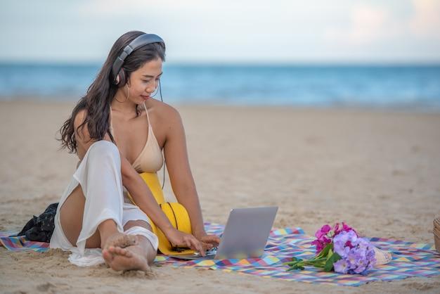 Uśmiechnięta atrakcyjna azjatycka kobieta z szczęściem i cieszyć się na plaży