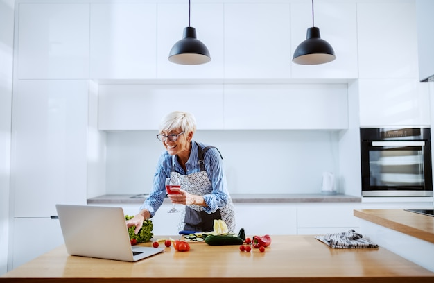 Uśmiechnięta atrakcyjna blond starsza kobieta w fartuchu używać laptop dla przepisu i pije wino