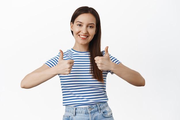 Uśmiechnięta atrakcyjna brunetka pokazuje kciuki do góry, kiwa głową z aprobatą, poleca sprzedaż, chwali dobry wybór, świetną robotę, zadowolona z czegoś, lubię i zgadzam się, biała ściana.