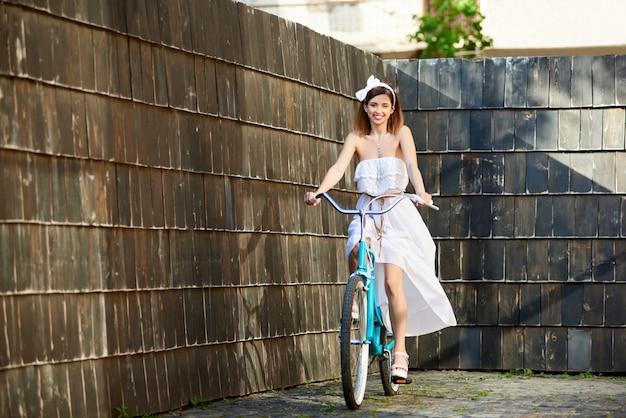 Uśmiechnięta atrakcyjna dziewczyna jedzie rocznika błękitnego rower na brukowanej ulicie z ciemnymi drewnianymi ścianami w pogodnym letnim dniu