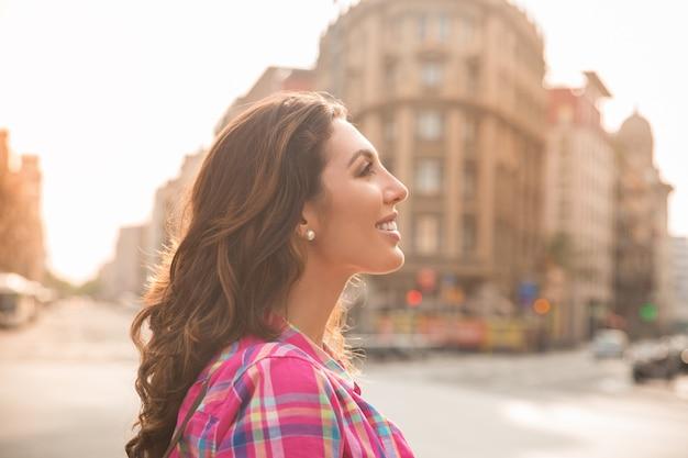 Uśmiechnięta atrakcyjna dziewczyna patrząc wkoło