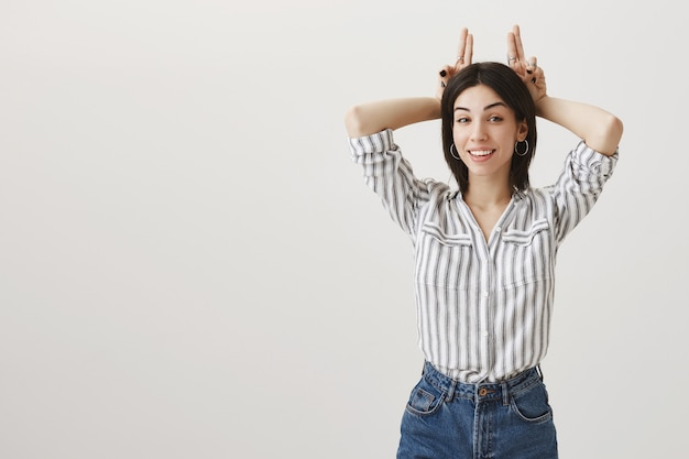 Uśmiechnięta atrakcyjna dziewczyna pokazuje gest rogi, jest uparta
