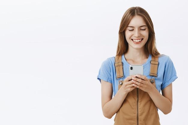 Uśmiechnięta atrakcyjna dziewczyna za pomocą telefonu komórkowego, wiadomości tekstowych lub przeglądania sieci społecznościowych