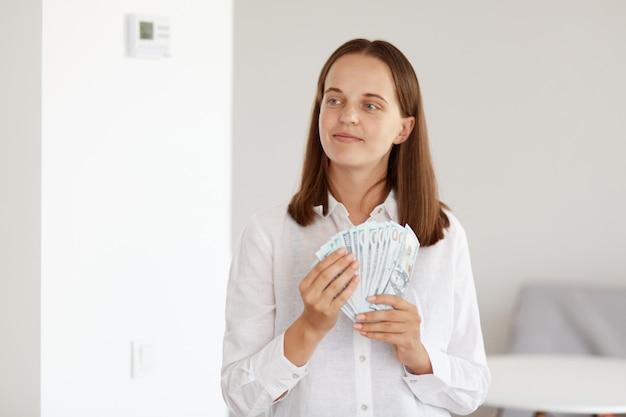 Uśmiechnięta atrakcyjna kobieta o ciemnych włosach, ubrana w białą koszulę w stylu casual, trzymająca w dłoniach wachlarz pieniędzy, odwracająca wzrok, planująca kupić drogi zakup.