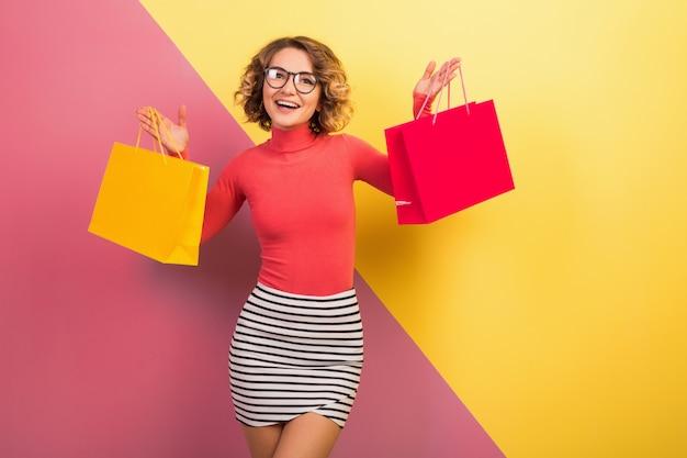Uśmiechnięta atrakcyjna kobieta podekscytowana w stylowy kolorowy strój trzymając torby na zakupy