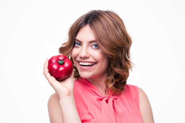 Uśmiechnięta atrakcyjna kobieta trzyma pomidora