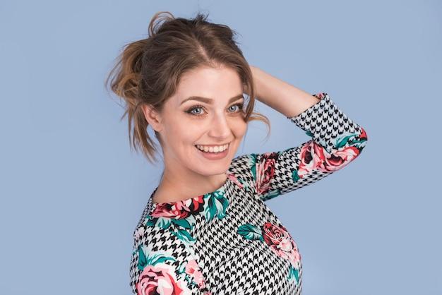 Uśmiechnięta atrakcyjna kobieta w eleganckiej sukni