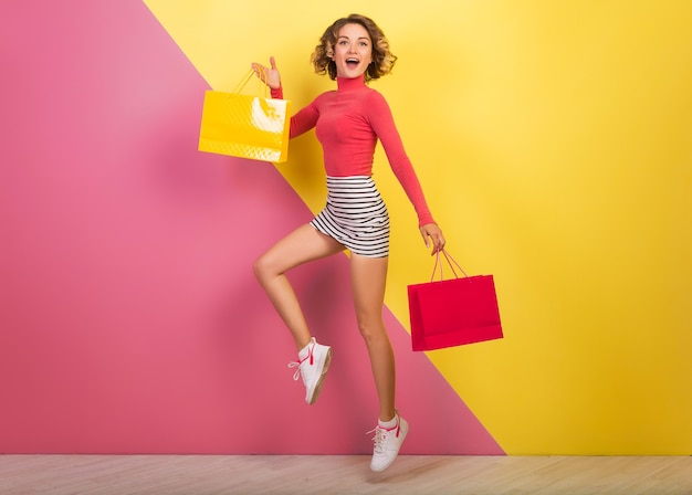 Uśmiechnięta atrakcyjna kobieta w stylowym, kolorowym stroju skaczącym z torby na zakupy, szczęśliwe, różowe żółte tło, golf, mini spódniczka w paski, wyprzedaż, dyskoteka, zakupoholiczka, moda na lato, emocjonalny