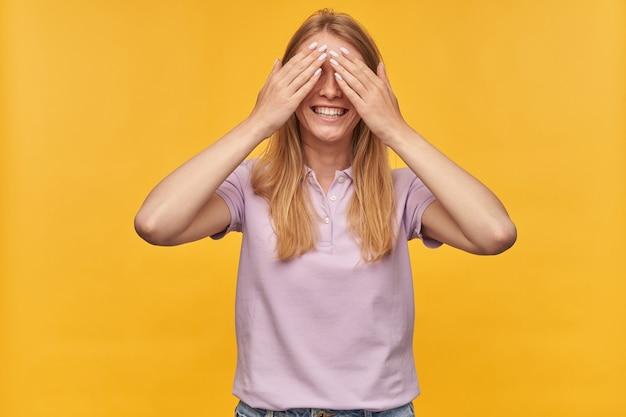Uśmiechnięta atrakcyjna kobieta z piegami w lawendowej koszulce stożkowatych oczach rękami i zabawę na żółto