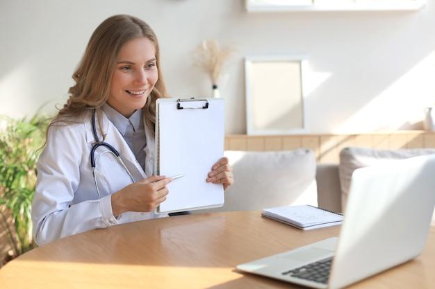 Uśmiechnięta atrakcyjna lekarka rozmawia przez kamerę z pacjentem.