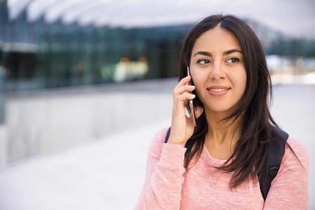 Uśmiechnięta atrakcyjna młoda kobieta komunikuje się na telefonie komórkowym