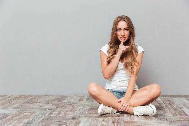 Uśmiechnięta atrakcyjna młoda kobieta pokazuje gest ciszy, siedząc na podłodze nad szarą ścianą