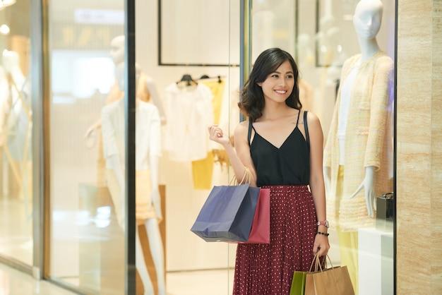 Uśmiechnięta atrakcyjna młoda kobieta spacerująca po centrum handlowym z wieloma papierowymi torbami w rękach