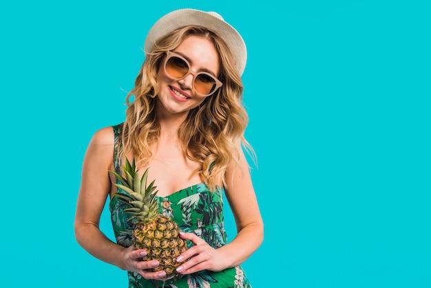 Uśmiechnięta atrakcyjna młoda kobieta trzyma świeżego ananasa w sukni z kapeluszem i okularami przeciwsłonecznymi