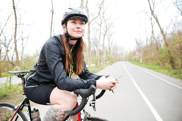 Uśmiechnięta atrakcyjna młoda kobieta w kasku rowerowym na rowerze za pomocą smartfona