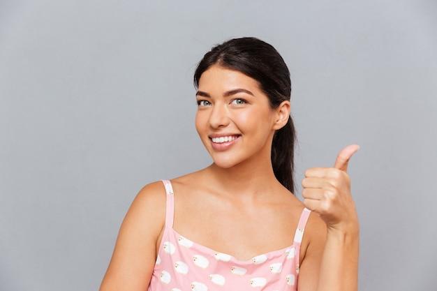 Uśmiechnięta atrakcyjna młoda kobieta wskazująca palcem z przodu na szarej ścianie