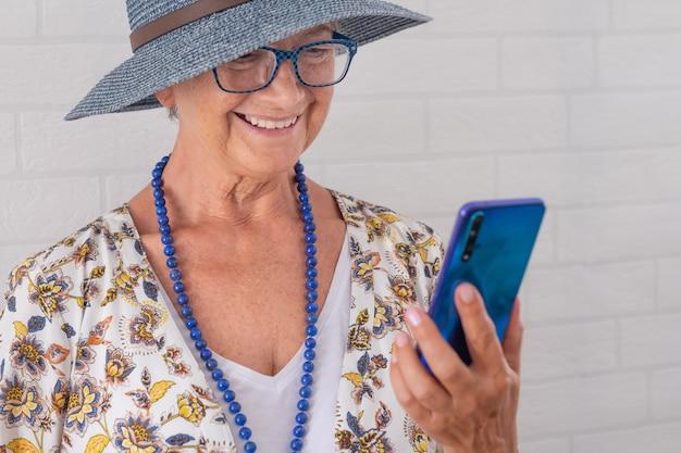 Uśmiechnięta atrakcyjna starsza kobieta w niebieskim kapeluszu, korzystająca z telefonu komórkowego - stojąca przy białej ceglanej ścianie - starsi ludzie korzystający z technologii