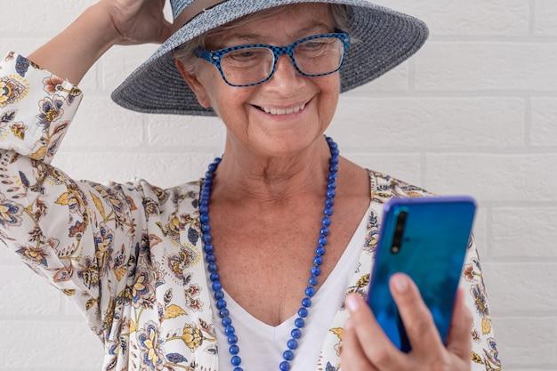 Uśmiechnięta atrakcyjna starsza kobieta w niebieskim kapeluszu, korzystająca z telefonu komórkowego stojącego przy ścianie z cegły