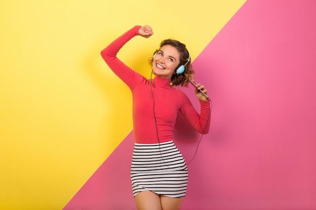 Uśmiechnięta atrakcyjna uśmiechnięta podekscytowana kobieta w stylowym, kolorowym stroju, taniec i słuchanie muzyki w słuchawkach na różowym żółtym tle, trend lato moda