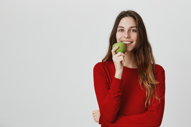 Uśmiechnięta atrakcyjna zdrowa kobieta jedzenie zielonego jabłka