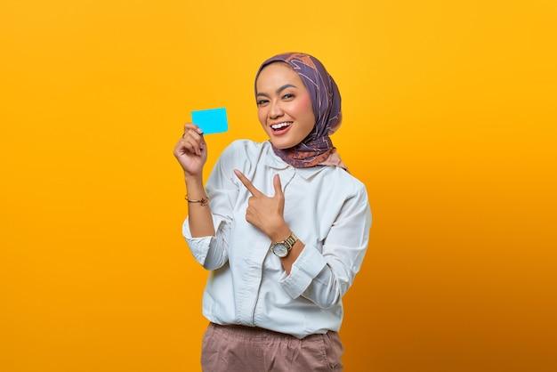 Uśmiechnięta azjatka pokazuje palcem pustą kartę na żółtym tle