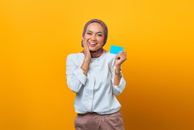 Uśmiechnięta azjatka trzymająca pustą kartę i dotykająca jej policzków na żółtym tle