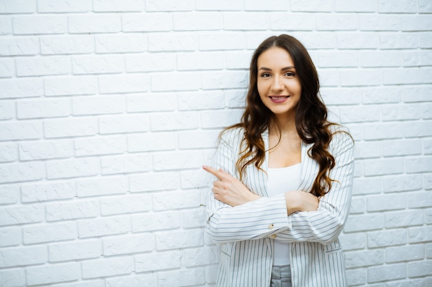 Uśmiechnięta azjatycka biznesowa kobieta wskazuje wierzchołek i patrzeje kamerę nad białym tłem