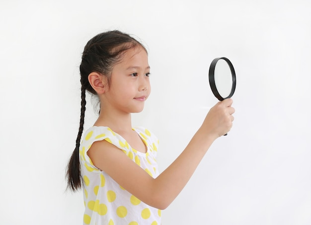 Uśmiechnięta azjatycka dziewczynka patrząca przez szkło powiększające obok na białym tle studyjnym .