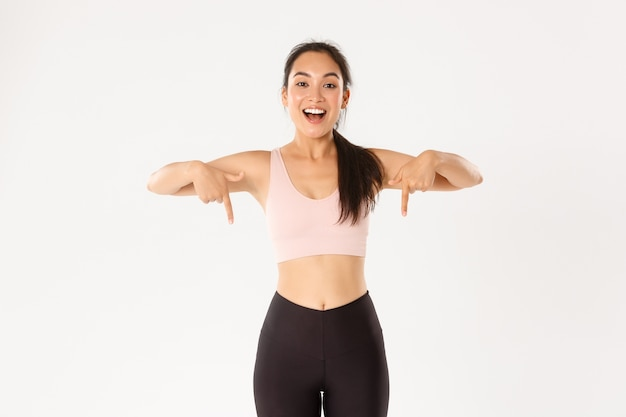 Uśmiechnięta azjatycka fitness dziewczyna pod napięciem, lekkoatletka zapraszająca na imprezę, pokazująca reklamę sprzętu treningowego, wskazująca palcami w dół, baner z logo.