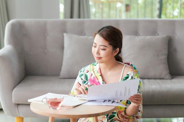 Uśmiechnięta azjatycka freelancerka pracująca w domu